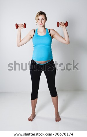 Pregnant woman exercising the shoulder muscles with dumbbells - stock photo