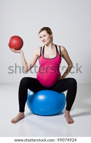Pregnant woman exercising with a red exercise ball while sitting on a blue fitness ball - stock photo