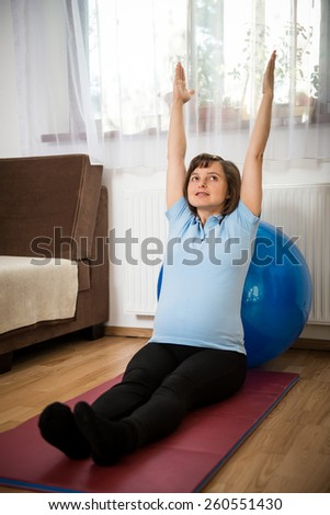Pregnant woman exercising with fit ball at home - stock photo