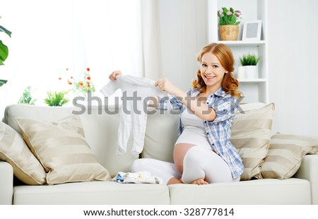 pregnant woman expectant mother prepares clothing items for the newborn baby - stock photo