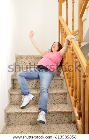 Pregnant Woman Falling Down On Stairs With Hands Up To Try Catching The Railing