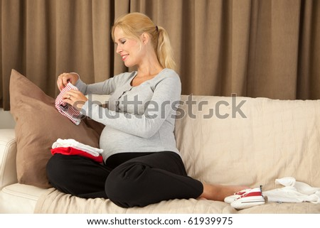 Pregnant woman folding little baby clothes on the couch