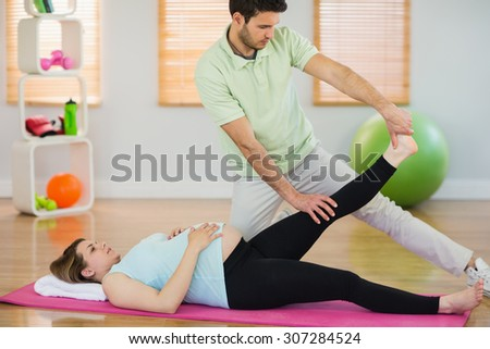 Pregnant woman getting relaxing massage in a studio - stock photo