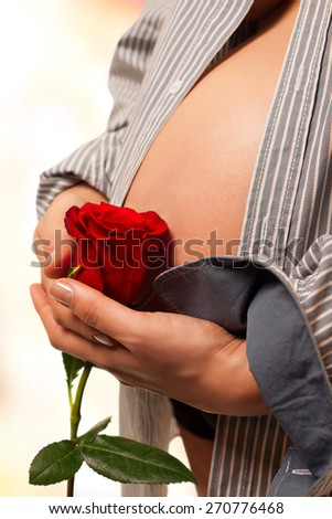 Pregnant woman hands holding a red rose in front of her abdomen. Image isolated with work path. - stock photo