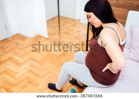 Pregnant woman having back aches  in the last trimester of pregnancy - stock photo