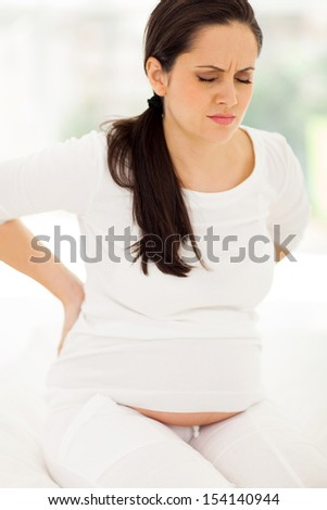 pregnant woman having back pain sitting on her bed