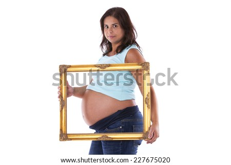 Pregnant woman holding a frame over her belly - stock photo