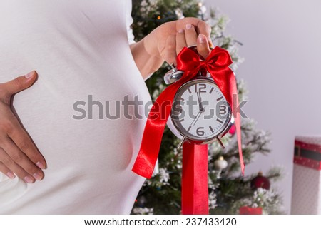 Pregnant woman holding alarm clock with ribbon - stock photo