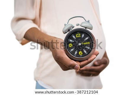 Pregnant woman holding an alarm clock on white background - stock photo