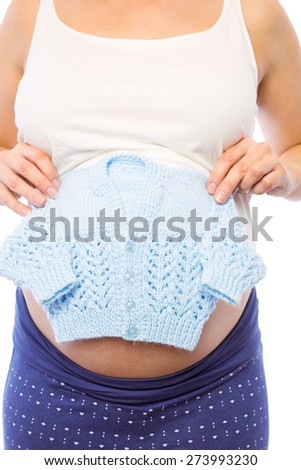 Pregnant woman holding baby clothes on white background