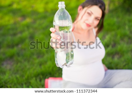 Pregnant woman holding bottle of water outdoors - stock photo