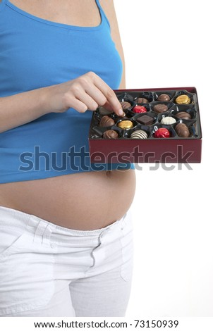 Pregnant woman holding box of chocolates (close up)