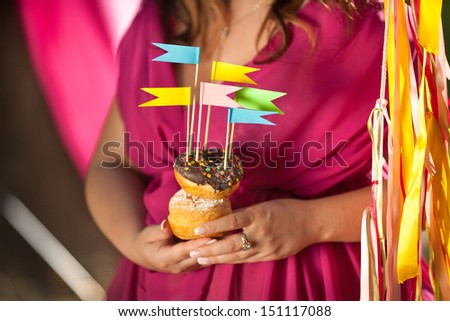 Pregnant woman holding Colorful donuts. girl with cake Donuts. Woman eating tasty donuts. Donuts at birthday party. Birthday. Party decoration. Colorful delicious donuts. Chocolate donuts unhealthy - stock photo