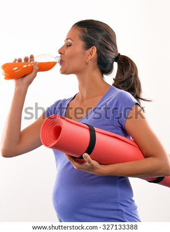 Pregnant woman holding exercise mat and drinking orange juice bottle after training - stock photo