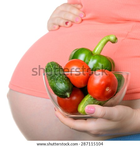 Pregnant woman holding fresh vegetables isolated on white background