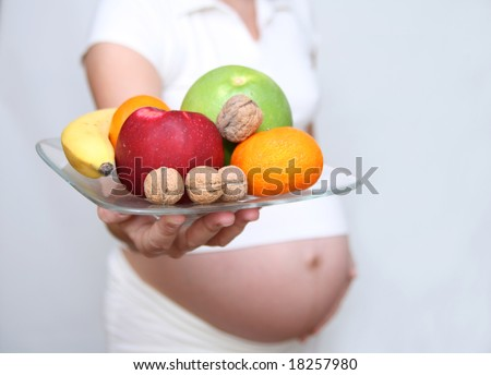 Pregnant woman holding fruits. Nine month. Third trimester