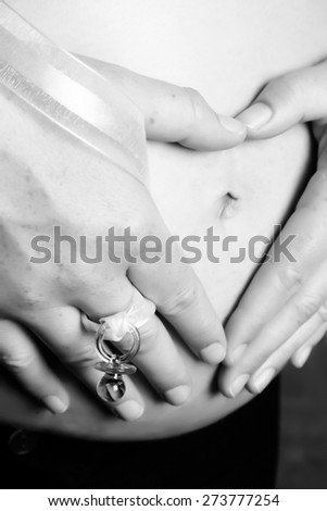 Pregnant woman holding her belly making a heart shape - stock photo