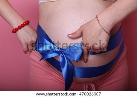 Pregnant Woman holding her hands in a heart shape on her baby bump. Pregnant Belly with fingers Heart symbol. Maternity concept. Baby Shower.