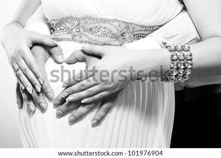 pregnant woman holding her tummy with father - stock photo