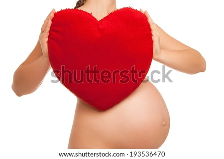 pregnant woman holding in her hands heart symbol over white