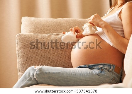Pregnant woman holding small baby shoes relaxing at home on couch