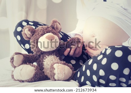 Pregnant Woman Holding Teddy Bear - stock photo