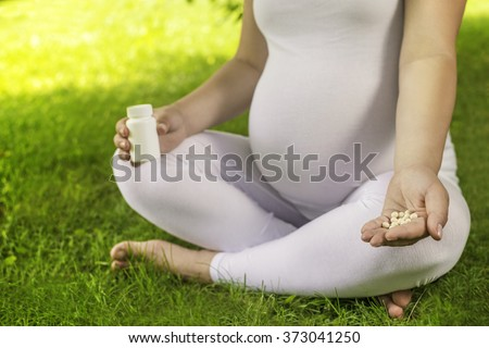 Pregnant woman holding vitamin pills in her hand and relaxing in nature on a beautiful sunny day