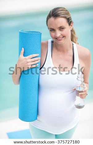 Pregnant woman holding water bottle and mat next to the swimming pool - stock photo