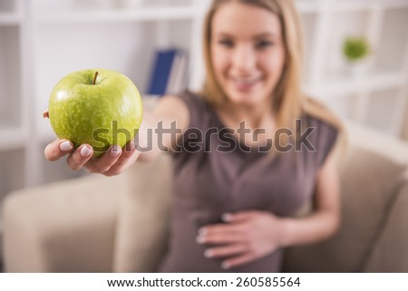Pregnant woman holds an apple is sitting on the couch. - stock photo
