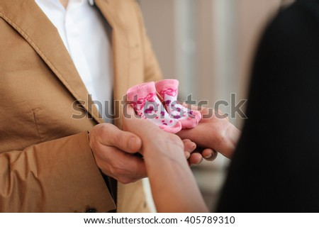 Pregnant woman holds pink booties. Beautiful pregnant woman and her husband in black dress and brown suit. Husband holds wife's hands with two booties. - stock photo
