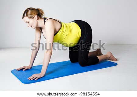 Pregnant woman in a four point kneeling position ready to exercise her core trunk muscles - stock photo