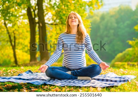Pregnant woman in a lotus position performs breathing exercises outdoors - stock photo