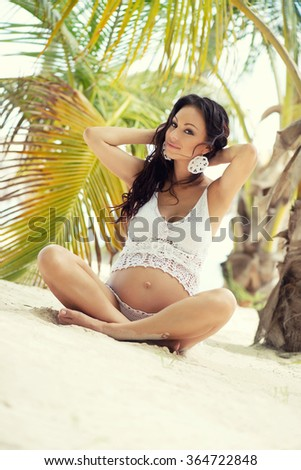 Pregnant woman in beautiful knit set on the sandy beach. Tropical exotic nature. - stock photo