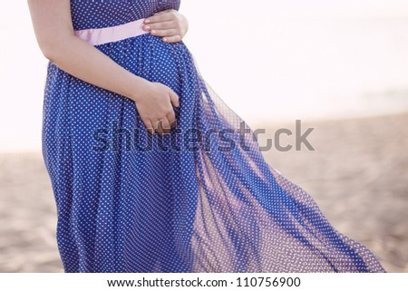 pregnant woman in blue dress developing on the wind. sunset - stock photo