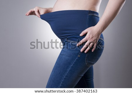 Pregnant woman in blue jeans on gray background. Side view
