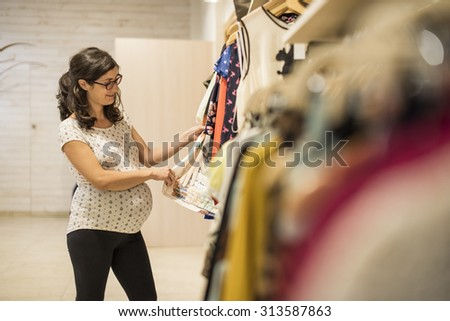 Pregnant woman in clothes store looking some clothes to buy