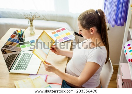 Pregnant woman in home office with laptop - stock photo