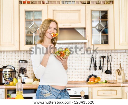 Pregnant woman in kitchen eating a salad - stock photo