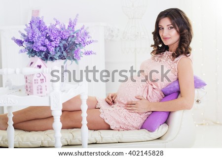 Pregnant woman in light room at home - stock photo