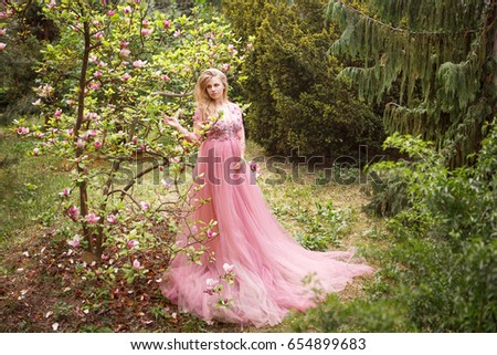 Pregnant woman in pink long dress standing blooming magnolia in forest . Beautiful future mother in romantic dress on nature. Blooming magnolia tree. Pregnant blonde in fashion dress
