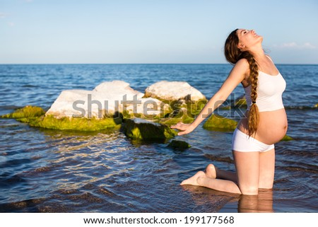 Pregnant woman in sports bra doing exercise in relaxation on yoga pose on sea. The concept of health and sport - stock photo