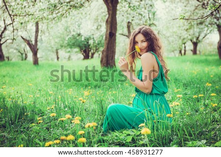 Pregnant woman in the apple orchard is holding dandelion