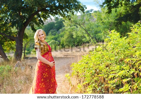 Pregnant woman in the park.Indian girl in dress - stock photo