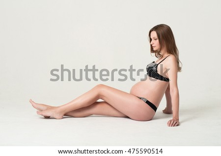 Pregnant woman in underwear sitting on the floor with one leg bent on neutral background