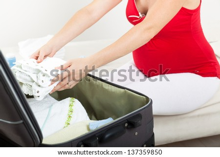 Pregnant woman is getting ready for the maternity hospital, packing baby clothes - stock photo