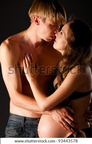 Pregnant woman is kissing with man on black background