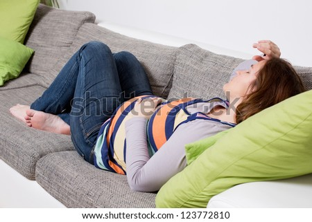 Pregnant woman laying on a sofa sleeping relaxed