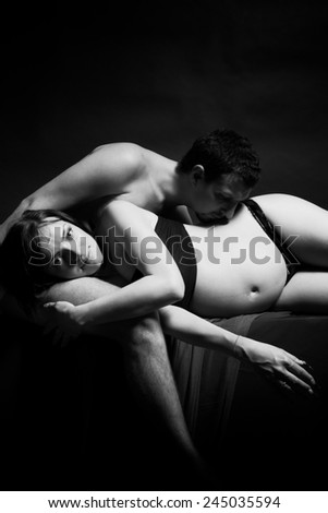pregnant woman lies on the hands of her husband, who kisses her belly. black and white - stock photo