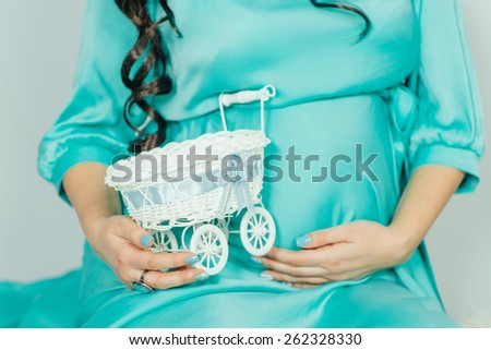 Pregnant woman looking at toy stroller - stock photo