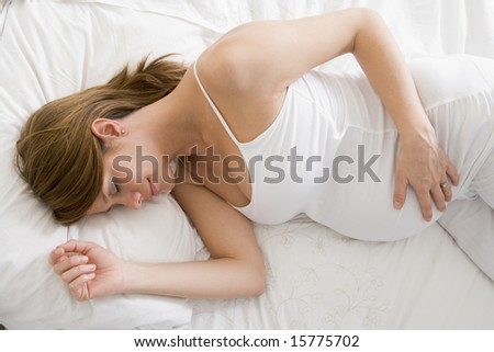 Pregnant woman lying in bed sleeping